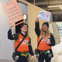 Two volunteers at the 50/50 Raffle wearing orange raffle penny shirts and holding signs that say 50/50