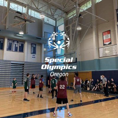 Photo of basketball game with Special Olympics Oreogn logo centered ad overlaid