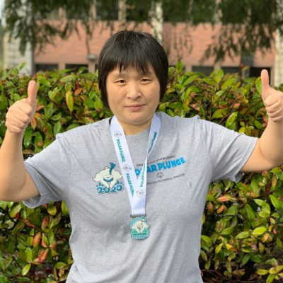 Irene Song wearing polar plunge 5k/10k medal and giving thumbs up to camera