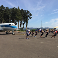 Team of people pulling a rope connected to a large plane
