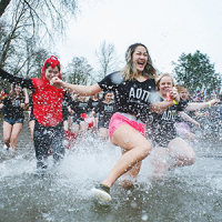 Photo of people running into water at on of Special Olympics Oregon's Polar Plunge events
