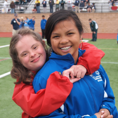 Athlete hugging Unified Partner and smiling at camera
