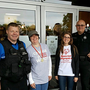 Special Olympics athletes and volunteers standing with members of the Portland Police force