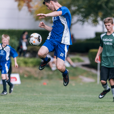 Soccer player high in the air kicking soccer ball at a Unified PE event