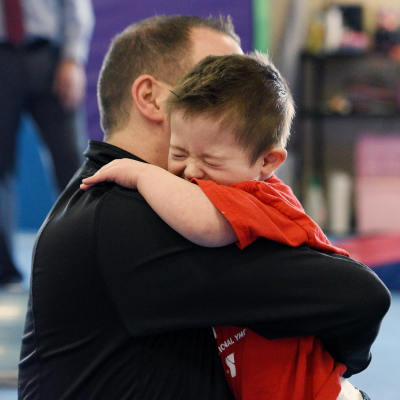 Young athlete hugging coach