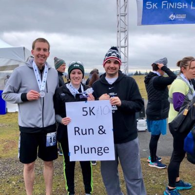 "Athlete Jack Kain with YPC member Marlo at the Polar Plunge 5K/10K finish line holding a white sign that reads ""5k/10K run & plunge"""