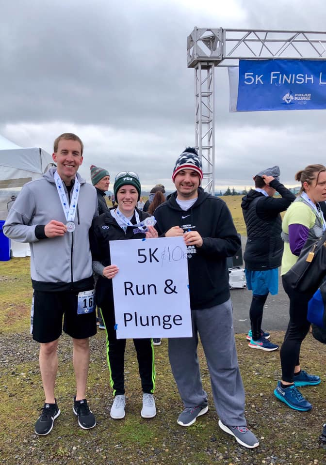 """Athlete Jack Kain with YPC member Marlo at the Polar Plunge 5K/10K finish line holding a white sign that reads """"5k/10K run & plunge"""""""