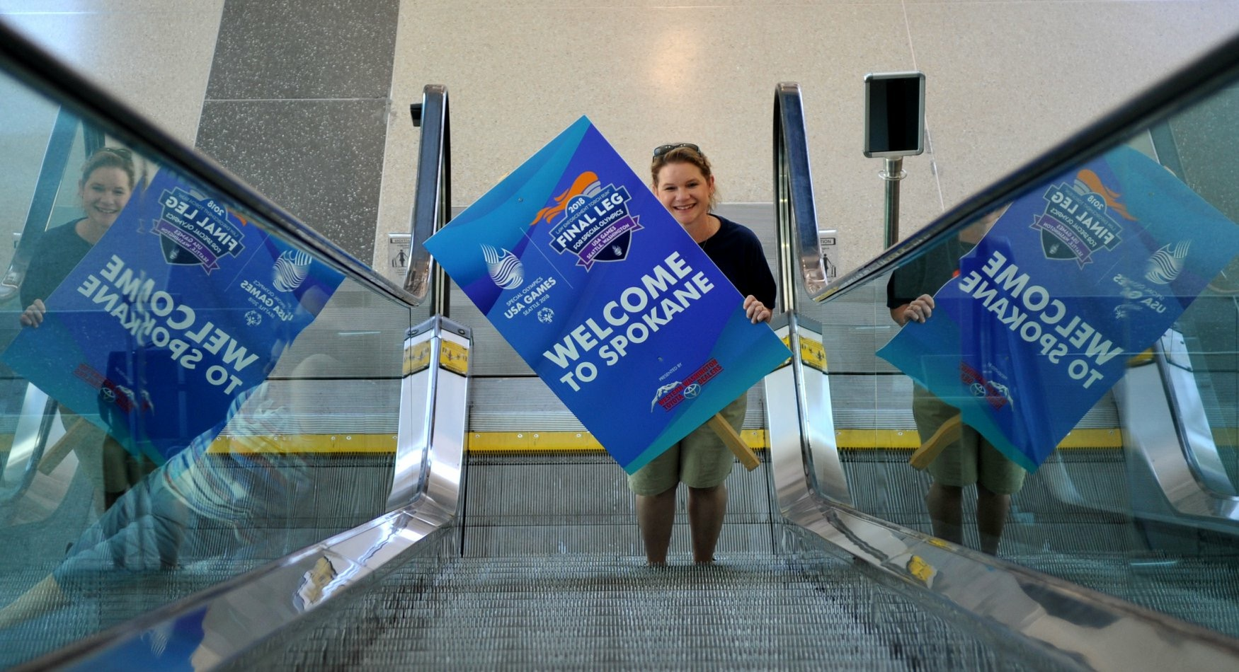 Tiffany holding a blue LETR signs that reads welcome to Spokane