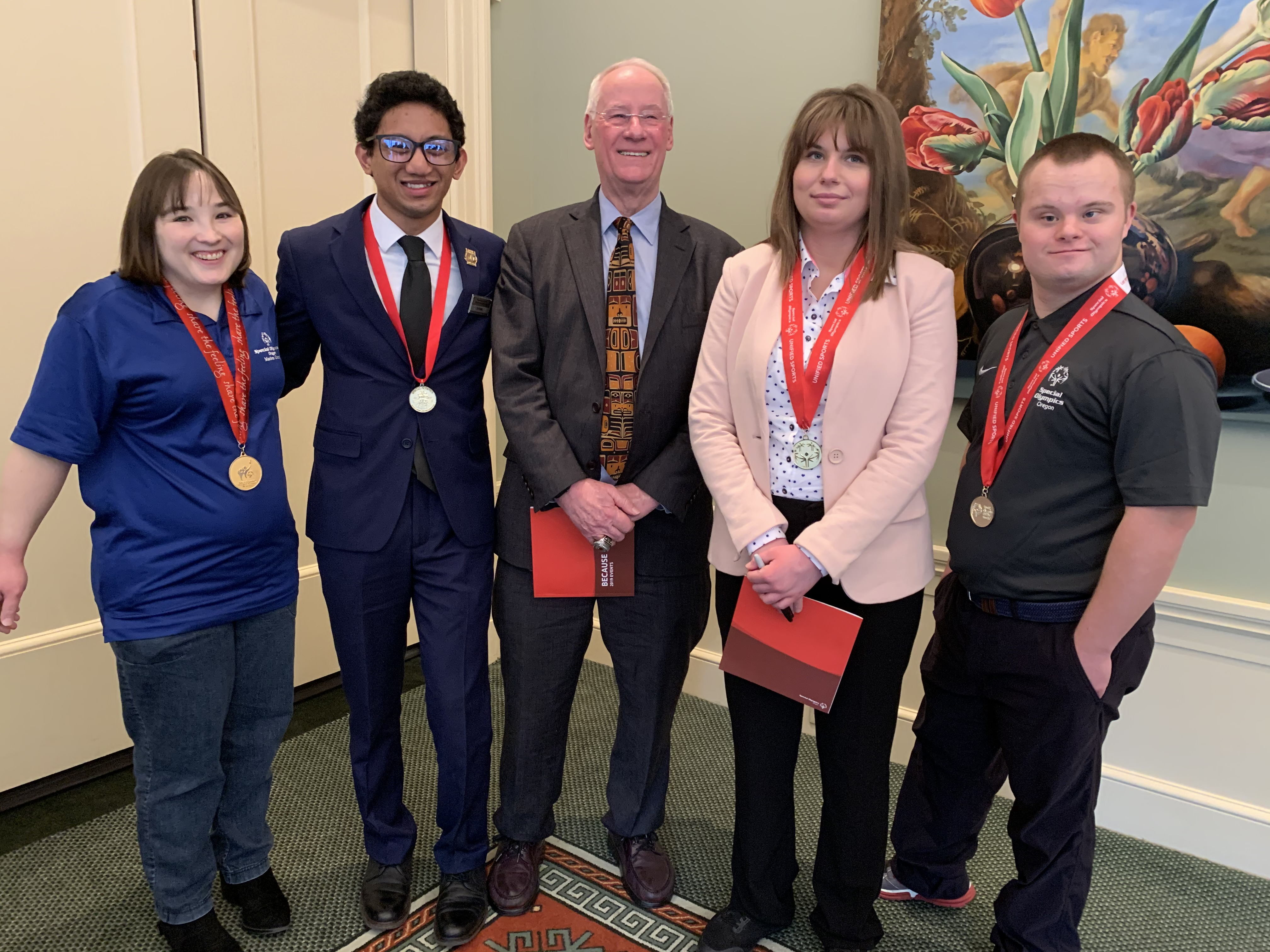 Dr. Ed Ray standing with 4 SOOR athletes