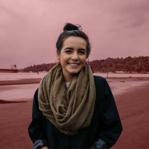 Staff member Meredith standing on the sand at the beach wearing a scarft with a red background