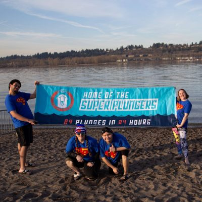 """Athletes holding a banner that reads """"Home of the Super Plungers. 24 plunges in 24 hours"""""""