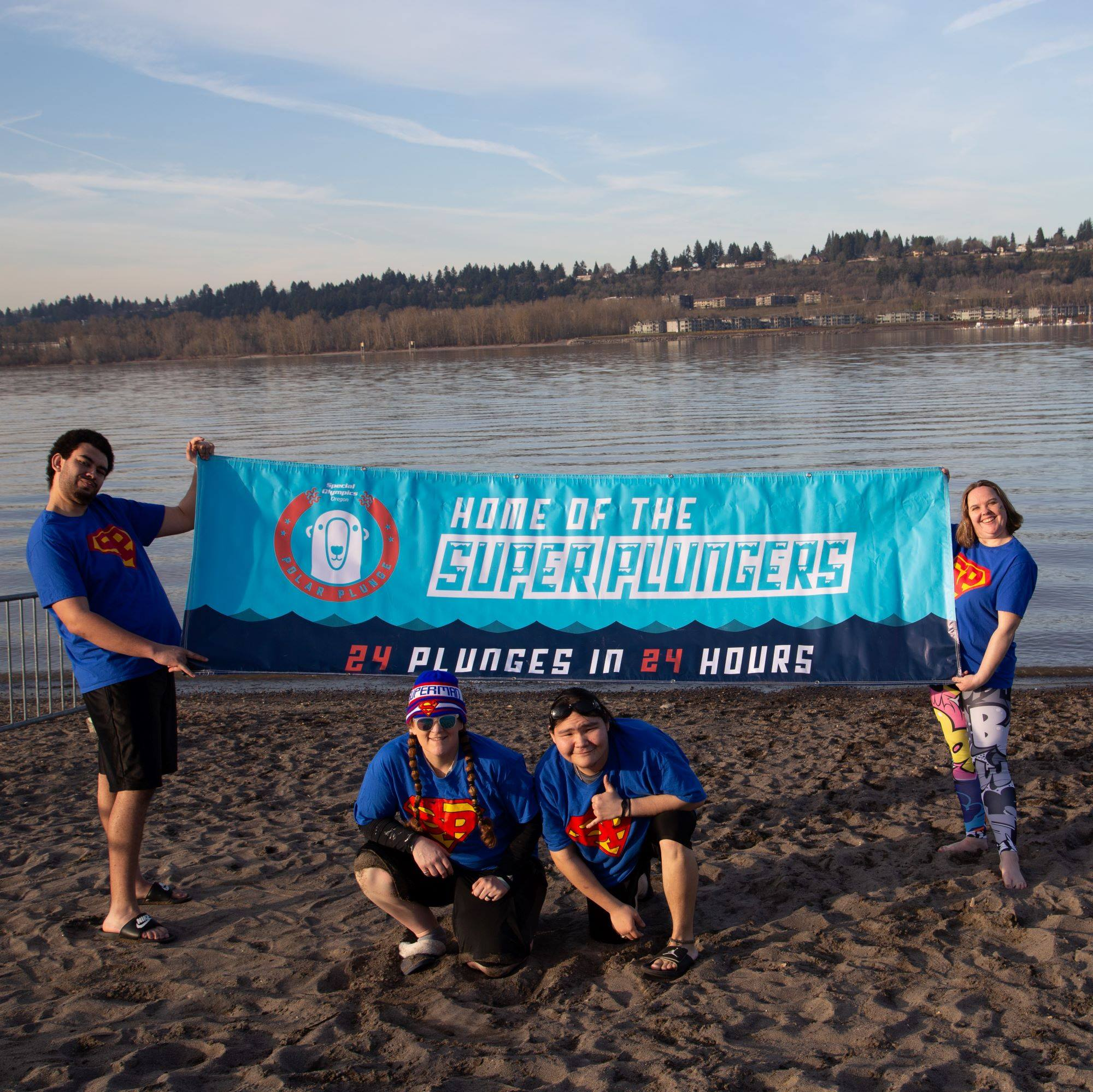 "Athletes holding a banner that reads ""Home of the Super Plungers. 24 plunges in 24 hours"""